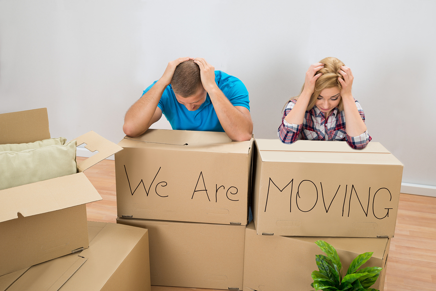 Frustrated Young Couple With Moving Boxes At Home